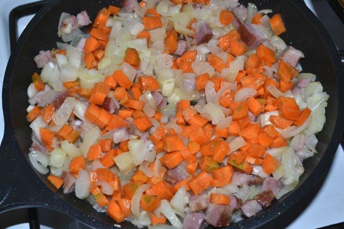 Лук, морковь и грудинка обжаренные на сковороде