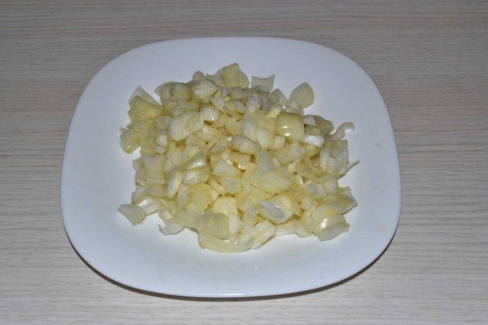 Очищенный и нарезанный лук на тарелке