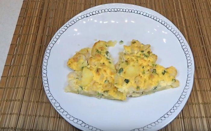 Омлет с картошкой и плавленым сыром на тарелке