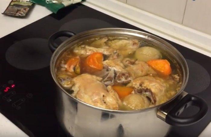 Лук, морковь и набор мяса для холодца в кастрюле