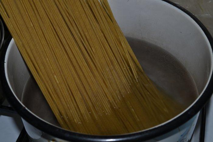 Целые спагетти опущенные в катрюлю с водой