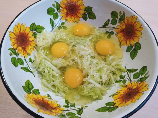 Четыре яйца в тарелке с тертым кабачком