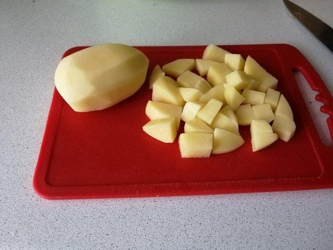 Картофель нарезанный кубиками на красной доске