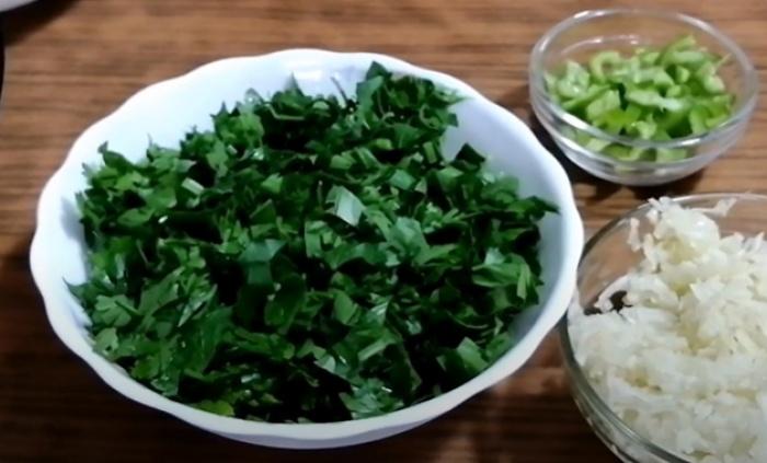 Зелень и горьки перец нарезанные в тарелке