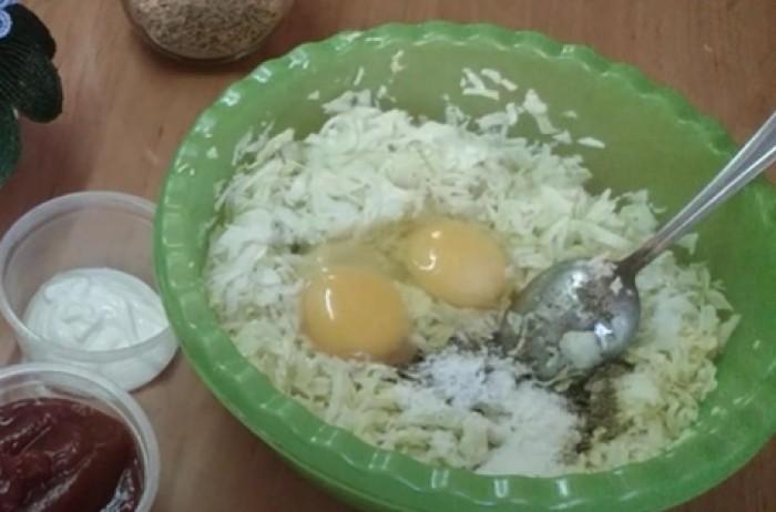 Измельченная капуста с яйцом и солью в миске