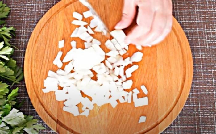 Лук нарезанный кубиками на круглой разделочной доске