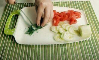Огуоец и помидор нарезанные на кусочки и шинкованная зелень на тарелке