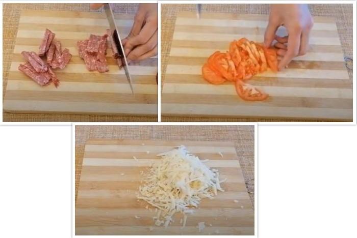 Тертый сыр с колбасой и резанными помидорами на разделочной доске